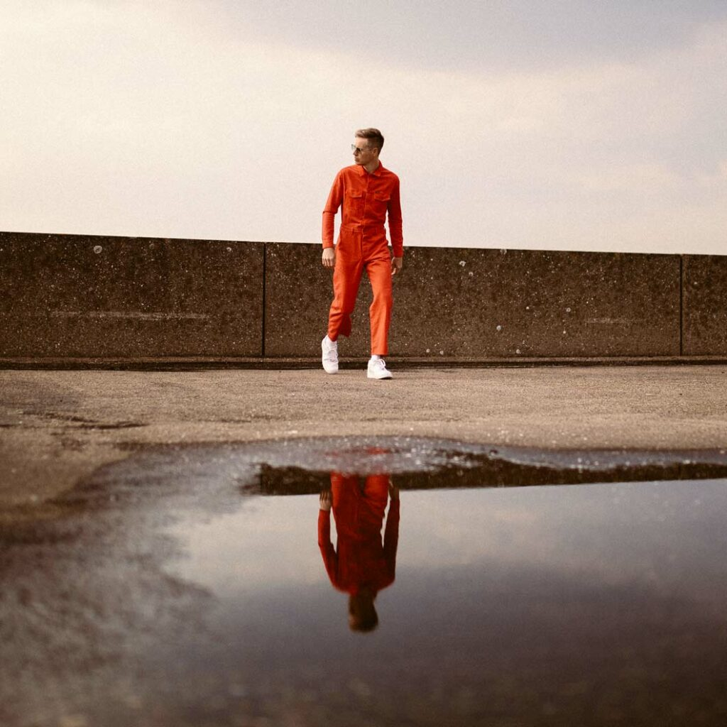 Joris Voorn reflected in large puddle.